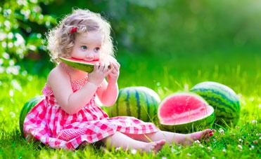 Bimba mangia un'anguria d'estate