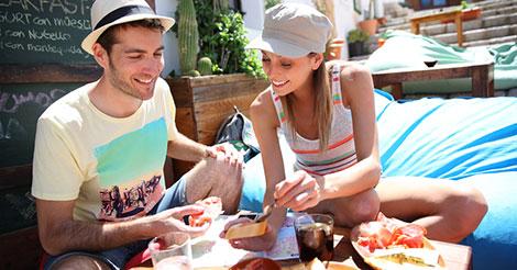 coppia in viaggio all'estero fa colazione all'aperto